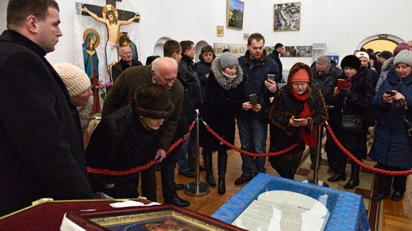 Прихожане фотографируют документ (томос) содержащий решение Священного Синода Вселенского патриархата о предоставлении автокефали УПЦ