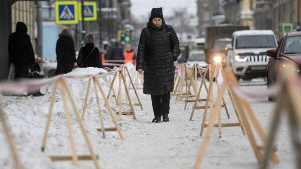Ограждения на Суворовском проспекте в Санкт-Петербурге, где работники коммунальных служб убирают снег с крыш домов