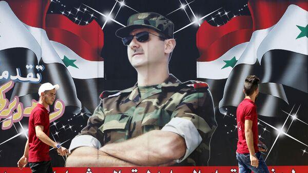 Сирийцы проходят мимо плаката с изображением Башара Асада в Дамаске