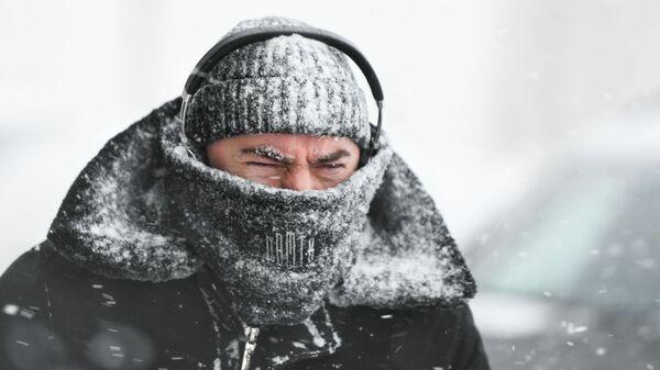 Прохожий во время снегопада в Москве