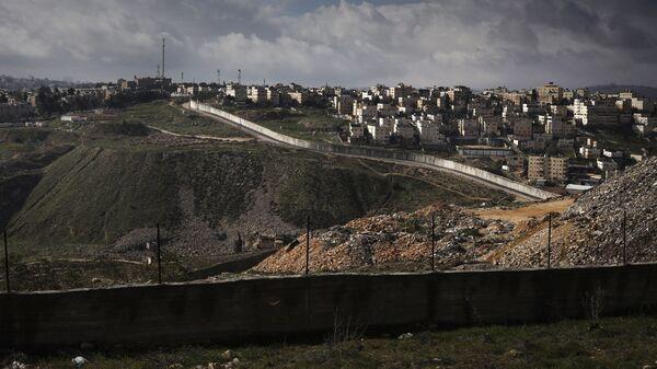 Вид на разделительный израильский барьер и поселение Неве Яаков в Восточном Иерасуламе из палестинской деревни Ал-Рам на Западном берегу реки Иордан. 17 января 2019