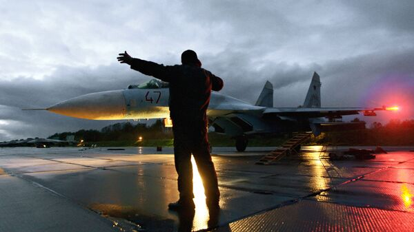 Военный техник дает отмашку на взлет истребителя Су-27 на аэродроме Чкаловск в Калининградской области