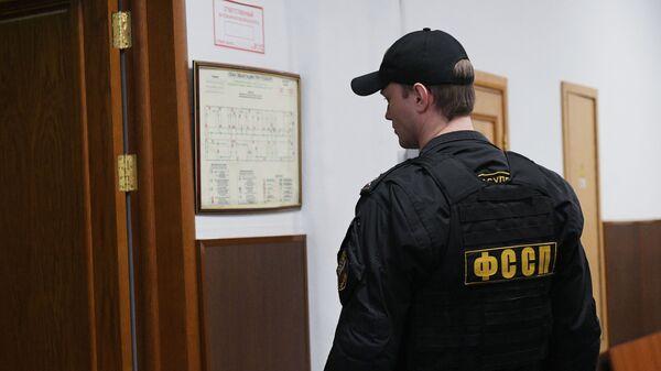 Сотрудник Федеральной службы судебных приставов (ФССП) в Басманном суде перед началом заседания по избранию меры пресечения задержанному сенатору Рауфу Арашукову. 30 января 2019