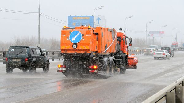 Снегоуборочная машина обрабатывает улицу противогололедным средством