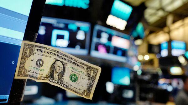 Долларовая банкнота прикреплена к экрану компьютера трейдера на Нью-Йоркской фондовой бирже