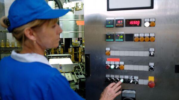 Сотрудница работает на линии разлива и фасовки подсолнечного масла