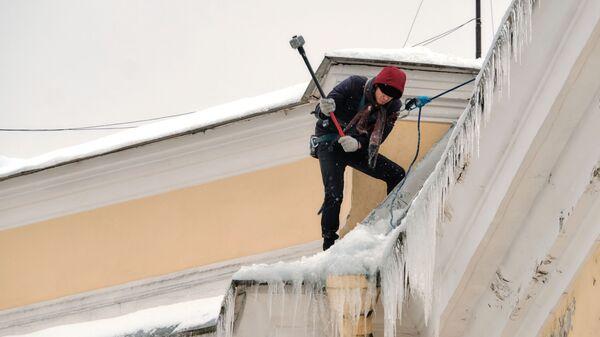 Работник коммунальной службы чистит от снега и сосулек крышу дома в Санкт-Петербурге
