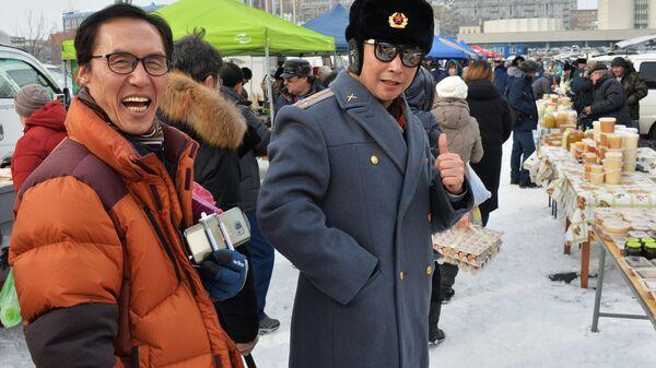 Туристы из Китая на продовольственной ярмарке на центральной площади Владивостока