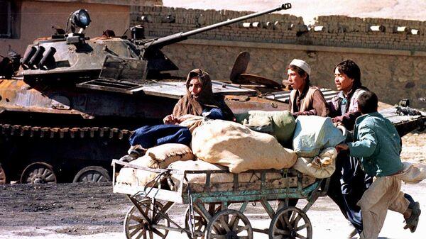 Афганские женщины идут мимо сгоревшего танка в Кабуле. 1996 год