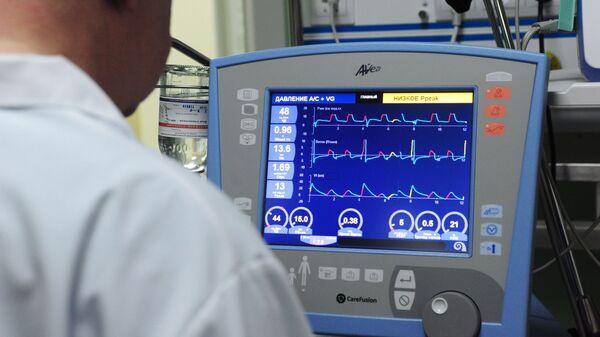 Врач корректирует параметры искусственной вентиляции легких на аппарате в отделении реанимации и интенсивной терапии