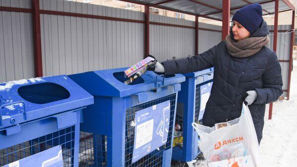 Женщина выбрасывает мусор в баки для раздельного сбора отходов в Московской области