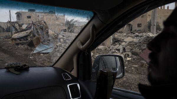 Бойцы Сирийских демократических сил (СДС) проезжают мимо разрушенных домов в деревне Аль-Сузах, в провинции Дейр-эз-Зор