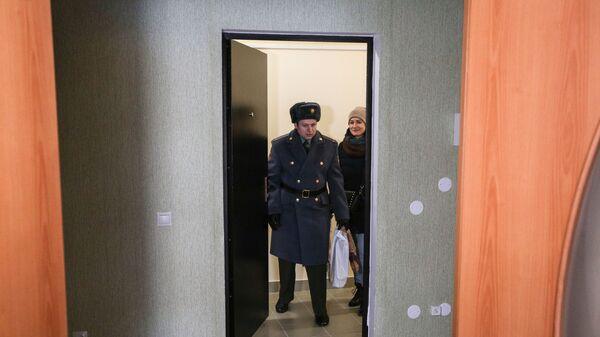 Новоселы заходят в свою новую квартиру после церемонии торжественной передачи служебного жилья военнослужащим войсковой части