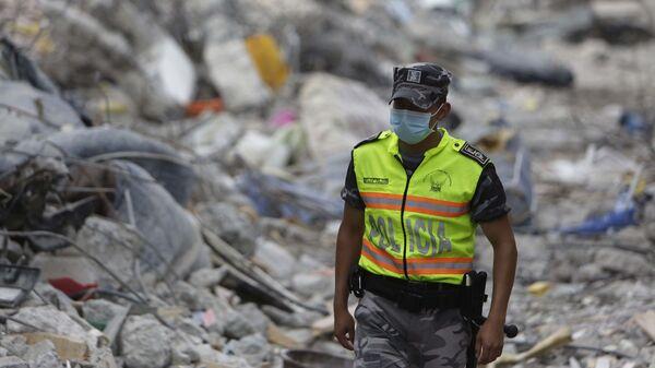 Полицейский после землетрясения в Эквадоре