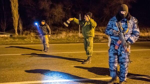 Сотрудник подразделения милиции специального назначения Беркут и казаки-добровольцы на блокопосту на въезде в Крым в районе Армянска