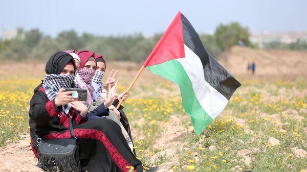 Девушки с флагом Палестины в городе Газа