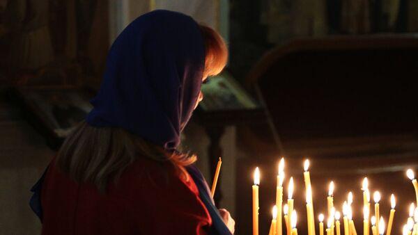 Женщина держит свечу во время богослужения