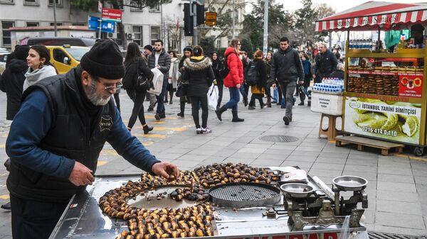 Мужчина продает жареные каштаны на одной из улиц Стамбула