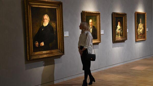 Девушка возле картины Портрет писателя И. С. Тургенева (1874 г.) на выставке Ильи Репина в Третьяковской галерее на Крымском валу в Москве