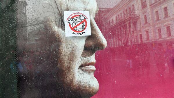 Стикер с надписью Свиней Порошенко за решетку на портрете президента Украины Петра Порошенко в Киеве