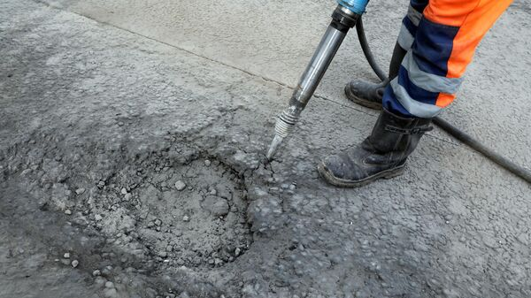 Рабочий бригады ГБУ Автомобильные дороги демонтирует старое дорожное полотно пневматическим отбойным молотком в Москве
