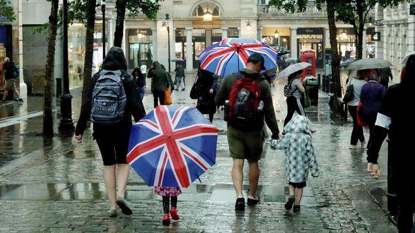 Дети с зонтами в цвет флага Великобритании на Ковент-гарден в Лондоне