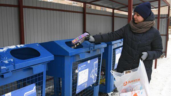 Женщина выбрасывает мусор в баки для раздельного сбора отходов