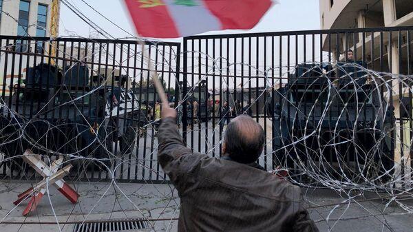 Участник акции протеста в связи с визитом в Ливан госсекретаря США Майка Помпео  у посольства США в пригороде Бейрута. 21 марта 2019