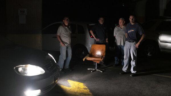 Мужчины на автомобильной стоянке во время отключения электроэнергии в Каракасе