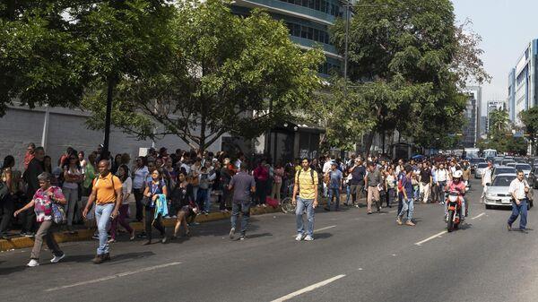Люди идут по улице в Каракасе во время второго отключения электроэнергии в городе
