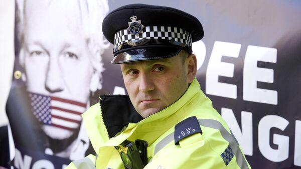 Полицейский рядом с баннером с изображением WikiLeaks Джулиана Ассанжа у Вестминстерского суда в Лондоне