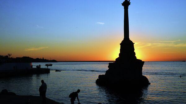 Отдыхающие у памятника затопленным кораблям в Севастополе