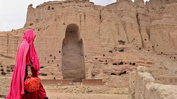 Женщина проходит мимо скал в Бамианской долине, где были высечены статуи. 2010 год