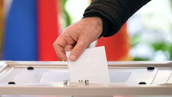 Избиратель опускает бюллетень в урну для голосования