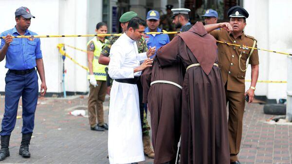 Священнослужители у входа в церковь в Коломбо, где произошел взрыв. 21 апреля 2019