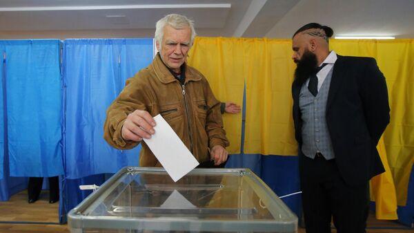 Житель Киева во время голосования на одном из избирательных участков города в день второго тура выборов президента Украины