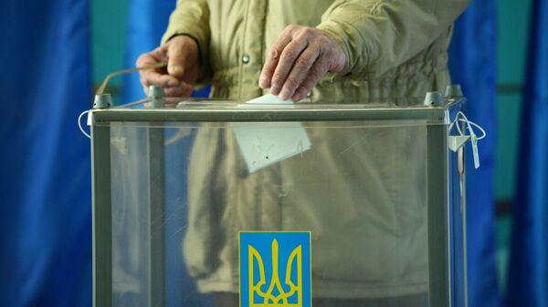 Избиратель во время голосования на одном из избирательных участков города Харькова
