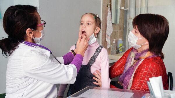 Врач проводит осмотр ребенка в детской поликлинике