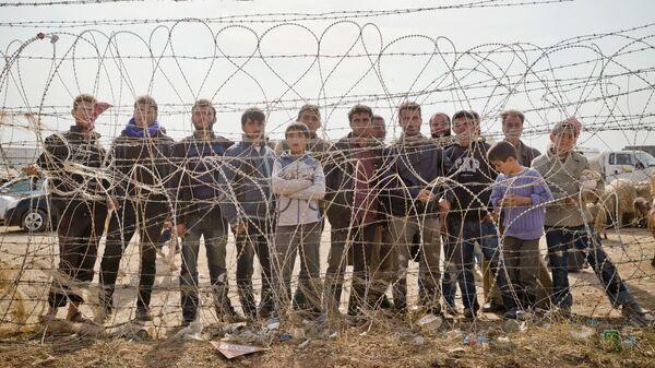 Сирийские курды стоят за забором, который обозначает турецко-сирийскую границу на окраине Кобани