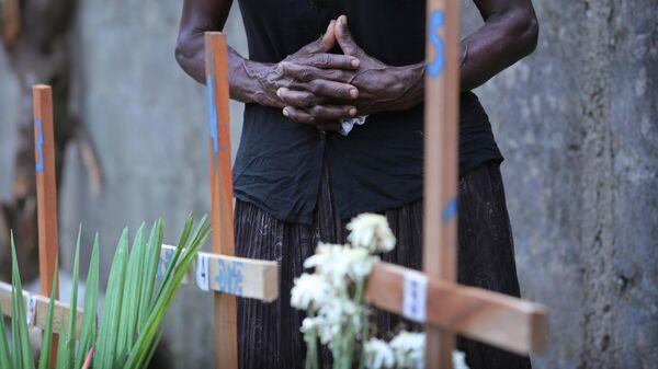 Женщина скорбит рядом с могилой родственника, погибшего во время взрывов в в Негомбо, Шри-Ланка