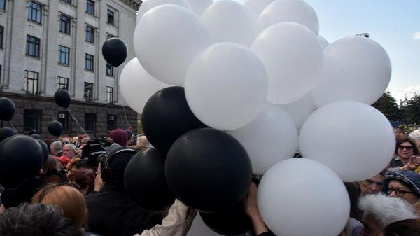 Жители Одессы несут воздушные шары к Дому профсоюзов во время траурных мероприятий, посвященных годовщине трагических событий 2 мая 2014 года