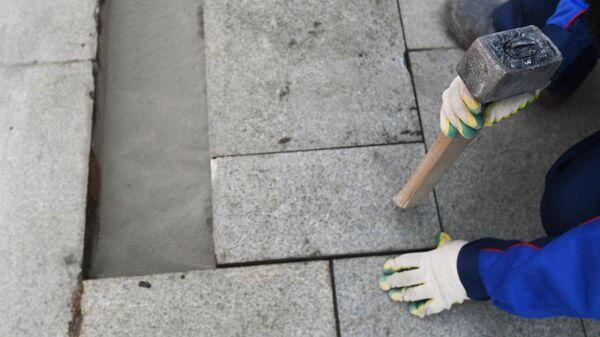 Рабочий укладывает тротуарную плитку