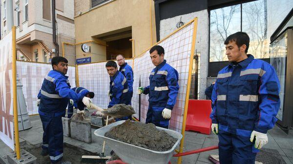 Рабочие укладывают тротуарную плитку на Никитском бульваре в Москве