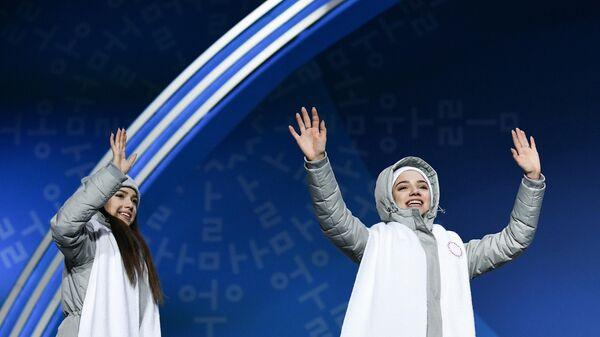 Российские фигуристки Евгения Медведева (справа) и Алина Загитова, завоевавшие серебряные медали в командных соревнованиях по фигурному катанию на XXIII зимних Олимпийских играх, во время церемонии награждения.