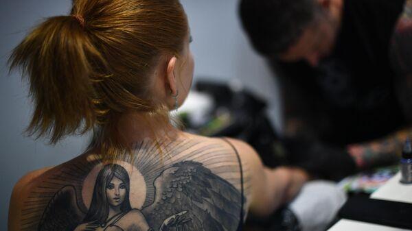 Мастер тату во время работы с моделью. Архивное фото