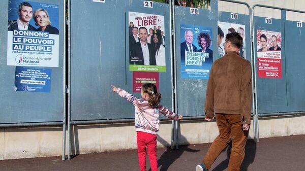 Избиратели у предвыборных плакатов кандидатов в заключительный день голосования на выборах в Европейский парламент у избирательного участка в Париже