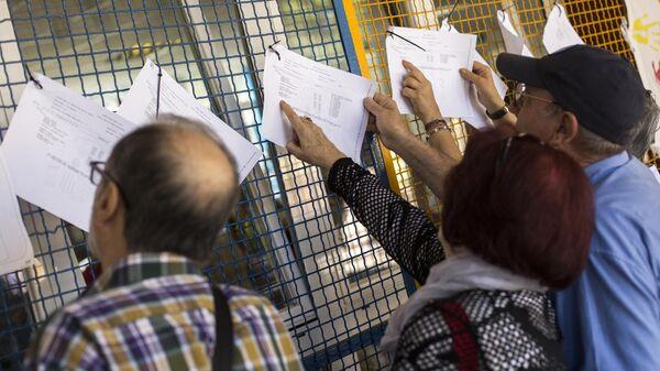 Люди ищут свое имя в избирательном списке на одном из избирательных участков в Мадриде в заключительный день голосования на выборах в Европейский парламент. 26 мая 2019