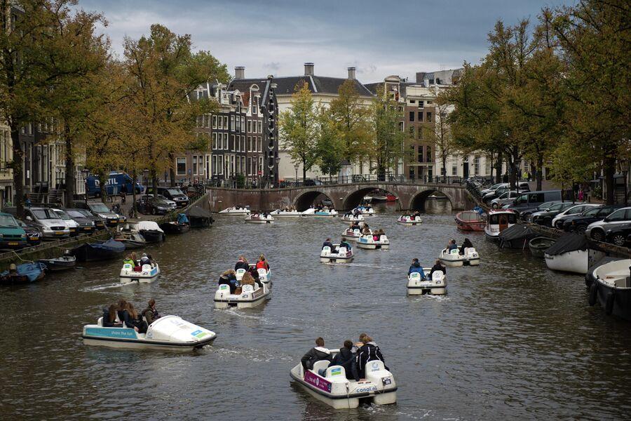 Туристы катаются на прогулочных катамаранах по каналу в центре Амстердама