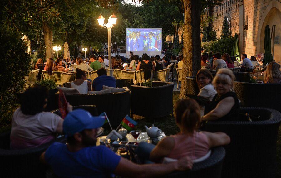 Люди смотрят трансляцию церемонии закрытия I Европейских игр в Баку в одном из уличных кафе