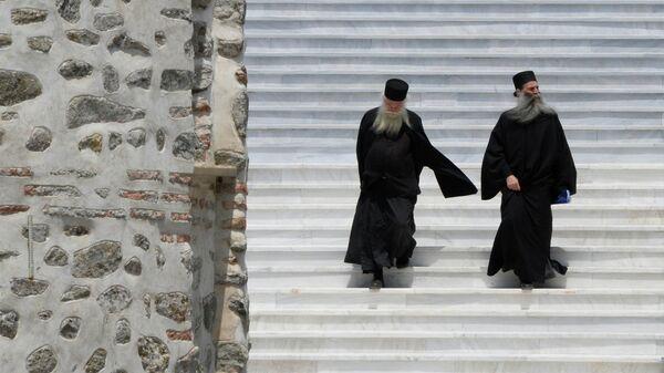 Священнослужители на лестнице здания Священного Кинота Святой Горы в городе Карее
